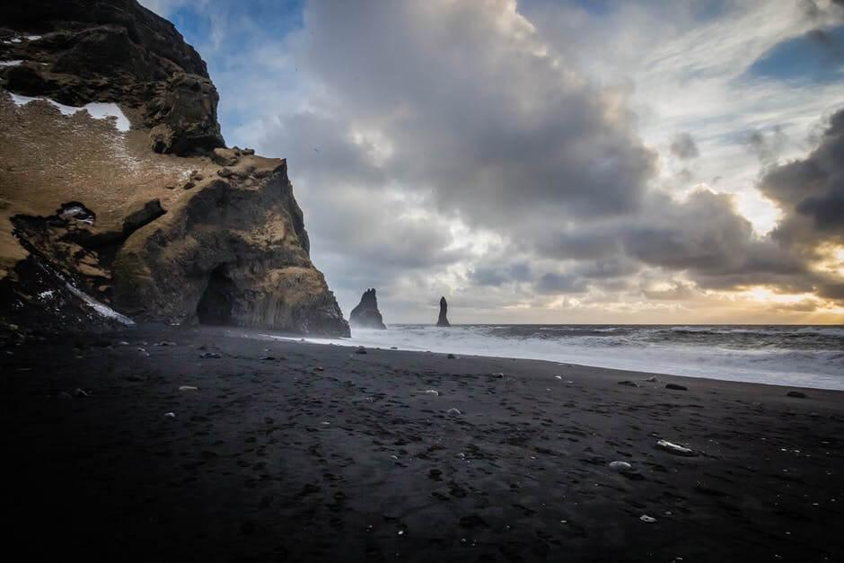 Czarna plaża wraz z nadmorskimi skałami