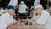 seniorzy grający w szachy w parku